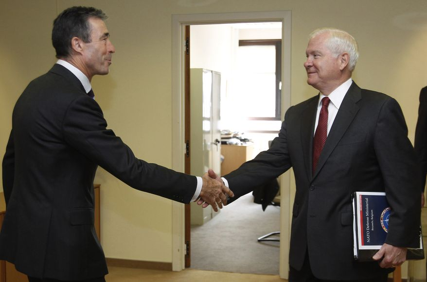 U.S. Secretary of Defense Robert M. Gates (right) shakes hands with NATO Secretary-General Anders Fogh Rasmussen at a meeting of NATO defense ministers in Brussels on Wednesday, June 8, 2011. (AP Photo/Jason Reed, Pool)