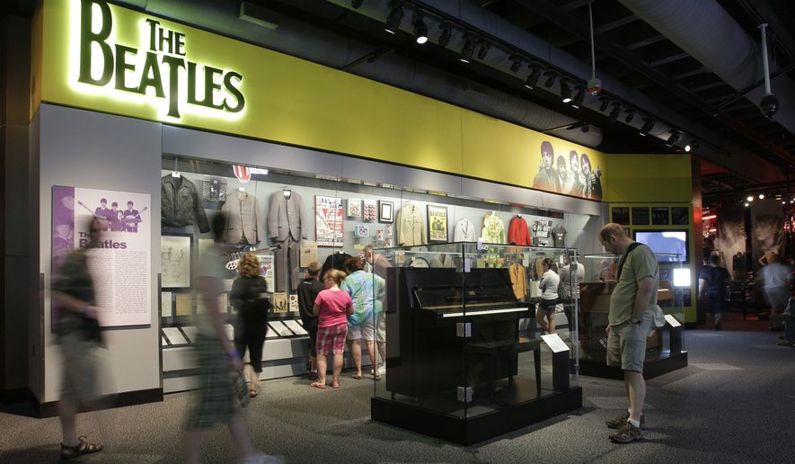 In this June 7, 2011, photo, visitors view an exhibit on The Beatles, at the Rock and Roll Hall of Fame and Museum in Cleveland. The Rock Hall says the exhibit is the world's largest collection of items from the group, as part of a redesign. (AP Photo/Mark Duncan)