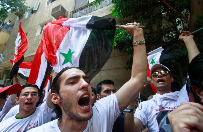 Syrian protesters carry national flags as they shout slogans against President Bashar Assad in front of the Syrian Embassy in Cairo on Tuesday, June 7, 2011. Syria's army has carried out days of deadly assaults to crush protesters calling for the end of Mr. Assad's rule. (AP Photo)