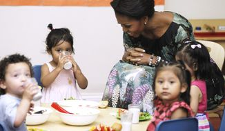 ** FILE ** First lady Michelle Obama sits with toddlers as they have their lunch at CentroNia, a bilingual child care facility in Washington, Wednesday, June 8, 2011, where she announced Let's Move! Child Care, an effort to raise healthy eating and living for young children. (AP Photo/Charles Dharapak)