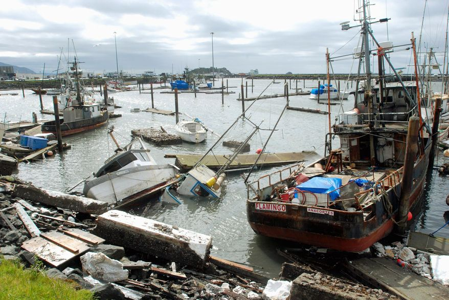 Sunken and damaged boats litter a basin at Crescent City the day after a powerful earthquake sent a tsunami across the Pacific Ocean. The surge of water broke up docks and bounced boats around the basin like billiard balls. (Associated Press)