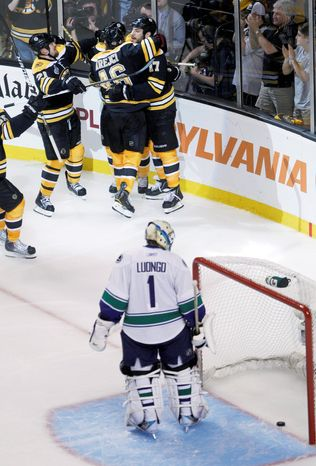 Boston Bruins center Rich Peverley, top, celebrates with teammates as Vancouver Canucks goalie Roberto Luongo (1) looks at the puck after Peverley scored in the third period during Game 4 of the NHL hockey Stanley Cup finals, Wednesday, June 8, 2011, in Boston. The Bruins won 4-0 to tie the best-of-seven series 2-2. (AP Photo/Charles Krupa)