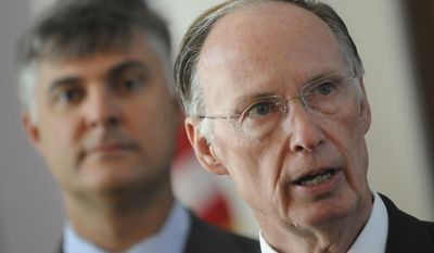Alabama Gov. Robert Bentley (right) speaks on Tuesday, June 9, 2011, at the Capitol in Montgomery, Ala., before signing into law what critics and supporters are calling the strongest bill in the nation cracking down on illegal immigration as Sen. Scott Beason, the bill's sponsor, listens. (AP Photo/Montgomery Advertiser)