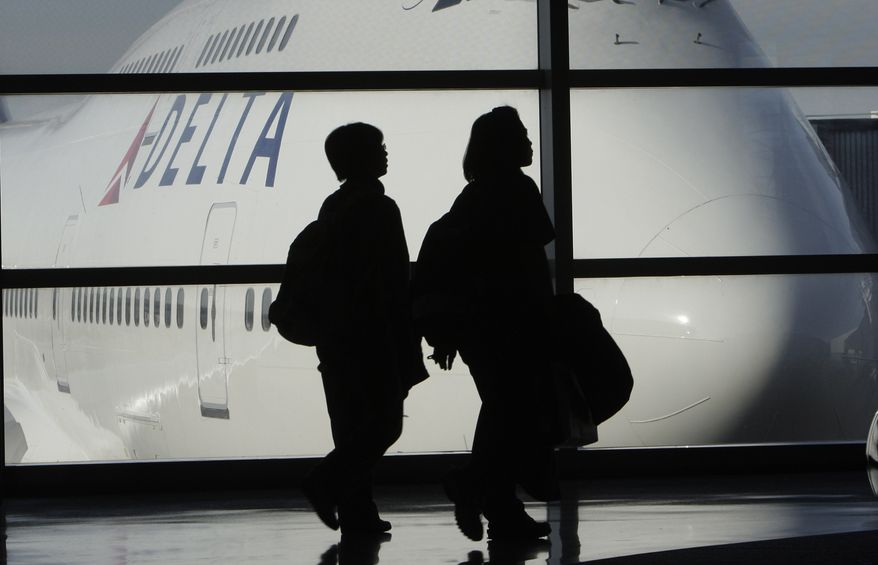 ** FILE ** Passengers walk past a Delta Air Lines Boeing 747 at the Detroit Metropolitan Wayne County Airport, one of Delta's hubs, in Romulus, Mich., in January 2010. (AP Photo/Paul Sancya, File)