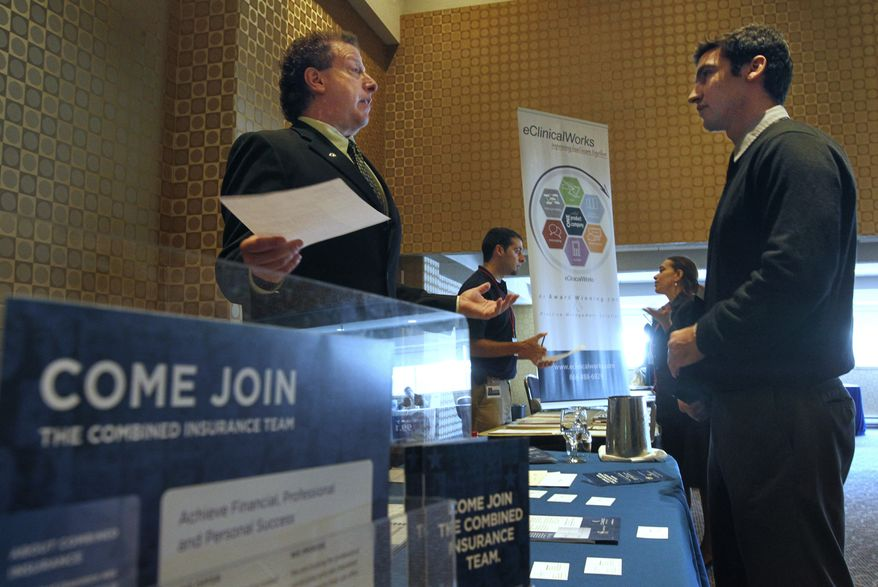 Mitchell Orenstein (left), market director for Combined Insurance, speaks with Gabriel Moraga of Somerville, Mass., at a job fair in Boston on Tuesday, June 7, 2011. (AP Photo/Steven Senne)