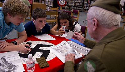 "From left, Daniel Buschor, 13, Tommy Bacon, 13, and Sara Berrios, 13, lean in to get a closer look at a photograph being held by World War II vet Richard Graff during their small-group interview with him at Rocky Run Middle School in Chantilly, Va.'s annual World War II Day, called ""The Latest Generation Meets the Greatest Generation,"" on Thursday, June 9, 2011. Graff also brought the Nazi flag that he managed to capture, which he and his platoon signed. (Barbara L. Salisbury/The Washington Times)"
