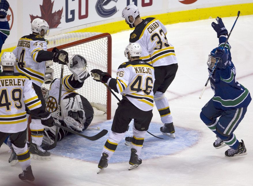 Vancouver Canucks center Manny Malhotra celebrates the first goal by teammate Maxim Lapierre, not shown, as Boston Bruins goalie Tim Thomas removes the puck from the net. The goal was enough to give the Canucks a 1-0 victory and 3-2 Stanley Cup finals lead. (AP Photo/The Canadian Press, Jonathan Hayward)