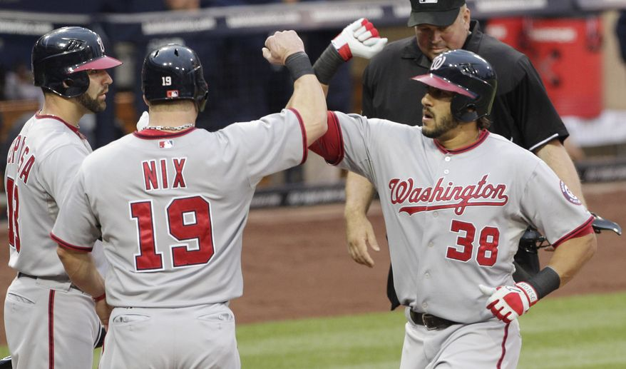 The Washington Nationals' Michael Morse is greeted at the plate by teammates Laynce Nix,  and Danny Espinosa after Morse hit a two-run home run against the San Diego Padres in the second inning. Those two runs were enough for the Nats in this one, as they hung on for the 2-1 victory. (AP Photo/Gregory Bull)