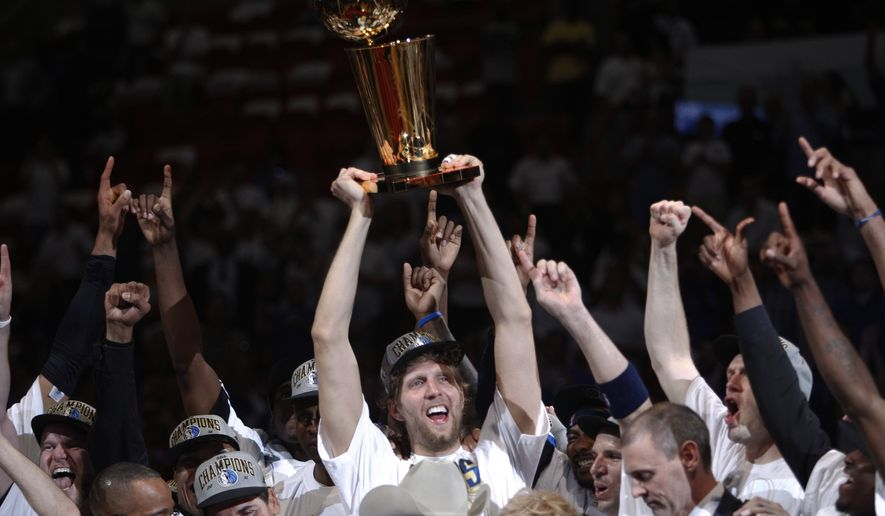 Dallas Mavericks' Dirk Nowitzki holds up the championship trophy after Game 6 of the NBA Finals basketball game against the Miami Heat Sunday, June 12, 2011, in Miami. The Mavericks won 105-95 to win the series. (AP Photo/Lynne Sladky)