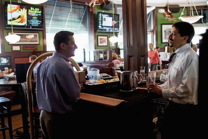 Dan Pollock, an operating partner at BlackFinn American Saloon in Bethesda, speaks with a bartender at his restaurant on Monday. The eatery, about five miles from Congressional Country Club, expects to be very busy this week with the U.S. Open being played on the Blue Course. (Pratik Shah/The Washington Times)