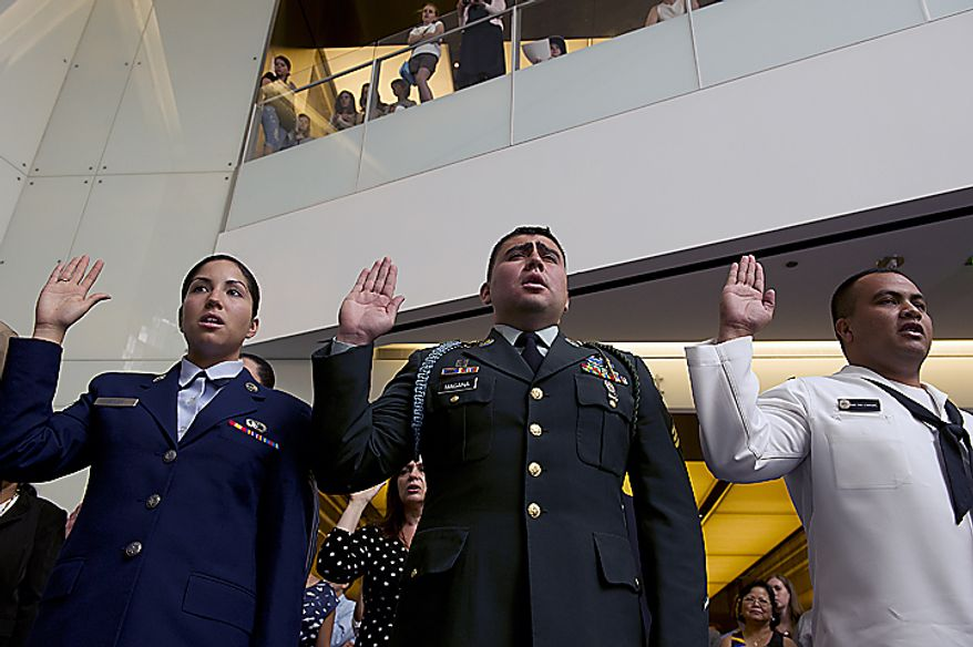 From left, Sr. Airman Deborah Vives, USAF, originally from Mexico, U.S. Army Sgt. Kelvin Magana, originally from El Salvador, and U.S. Navy sailor Hanlin Edwin, originally from Micronesia, take their oaths of citizenship on Flag Day, Tuesday, June 14, 2011 at the National Museum of American History in Washington, D.C. Twenty people from 12 different countries become naturalized American citizens  during the ceremony. (Barbara L. Salisbury/The Washington Times)