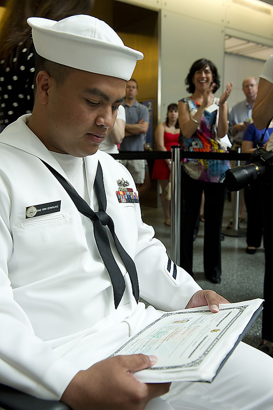 U.S. Navy sailor EM2 Hanlin Edwin, originally from Micronesia but now living in Washington, D.C., looks at his new certificate of naturalization as an on-looker claps after he and 20 others became naturalized U.S. citizens on Flag Day, Tuesday, June 14, 2011 at the National Museum of American History in Washington, D.C. Edwin was one of four new citizens who have already been serving in the U.S. Armed Forces. (Barbara L. Salisbury/The Washington Times)