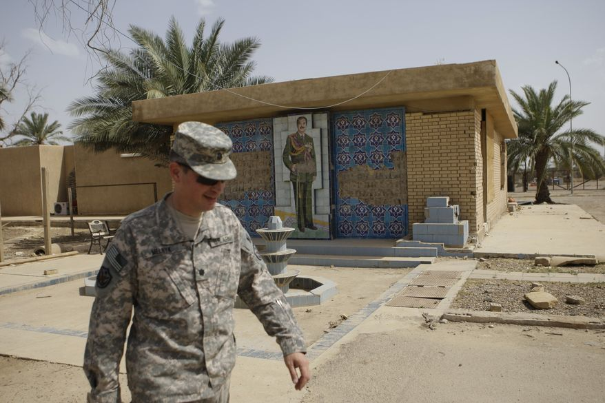 ** FILE ** Lt. Col. Les Melnyk, a U.S. military historian in Iraq, walks past a mural of the late Saddam Hussein in the Victory Base Complex in Baghdad on Tuesday, April 26, 2011. As the United States prepares to pull out its forces by Dec. 31, Hussein's palaces will be handed over to the Shiite-led Iraqi government that replaced the Sunni dictator. (AP Photo/Khalid Mohammed)