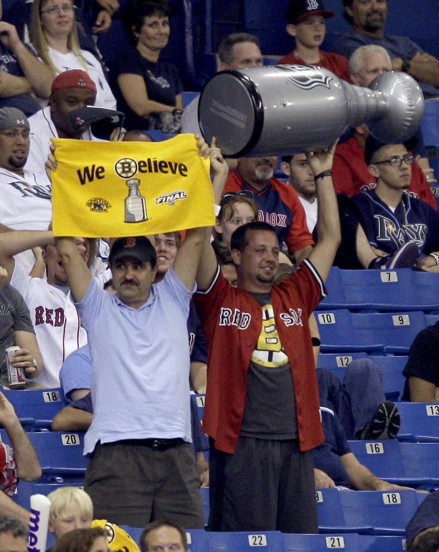 Boston Bruins fans hold up a towel and inflatable Stanley Cup during a baseball game between the Tampa Bay Rays and the Boston Red Sox on Tuesday, June 14, 2011, in St. Petersburg, Fla. The Bruins take on the Vancouver Canucks in Game 7 of the NHL hockey Stanley Cup Finals on Wednesday. The Rays defeated the Red Sox 4-0. (AP Photo/Chris O'Meara)