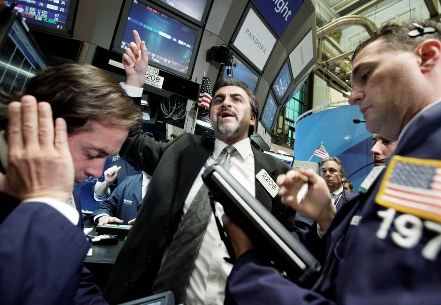 Specialist Jason Blatt (center) calls out prices for Pandora Media Inc. as it begins trading on the floor of the New York Stock Exchange on Wednesday. The IPO closed at $17.42, a gain of 8.9 percent. (Associated Press)
