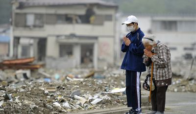 Kaisei Kubota and his grandmother, Yae, pray Saturday for victims in the northeastern Japanese town of Miyako, part of an area devastated by the March 11 tsunami. (Kyodo News via Associated Press)
