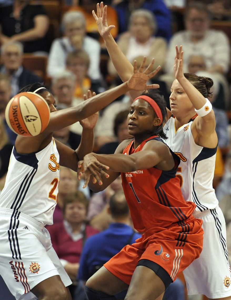 Washington Mystics' Crystal Langhorne, center passes while guarded by Connecticut Sun's DeMya Walker, left, and Kelsey Griffin, right, during the first half of a WNBA basketball game in Uncasville, Conn., on Saturday, June 4, 2011. (AP Photo/Jessica Hill)