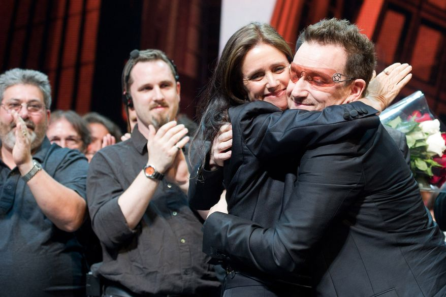 """Julie Taymor and Bono hug onstage during the curtain call of the opening-night performance of the Broadway musical """"Spider-Man: Turn Off the Dark"""" in New York on Tuesday, June 14, 2011. (AP Photo/Charles Sykes)"""