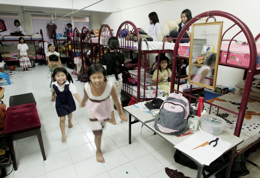 ASSOCIATED PRESS Myanmarese refugee girls play in their shared room in a suburb of Kuala Lumpur, Malaysia. Under a deal still being negotiated, 4,000 refugees in Malaysia would be moved to Australia and 800 illegal asylum-seekers in Australia would be sent to Malaysia.