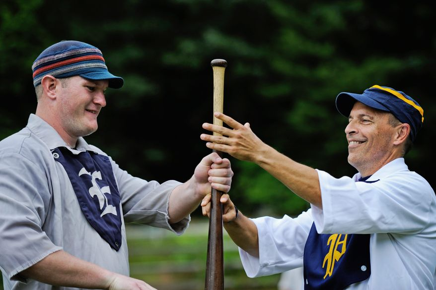"Elkton Eclipse outfielder Glyn ""Hammer"" Richards (below, left) of Mount Ephraim, N.J., and J.D. Almond do the ""bat toss"" before the start of the game. The winner of the hand-over-hand action chooses if his team will field or hit first. Players of vintage baseball don't wear gloves in the field and batters don't wear helmets."