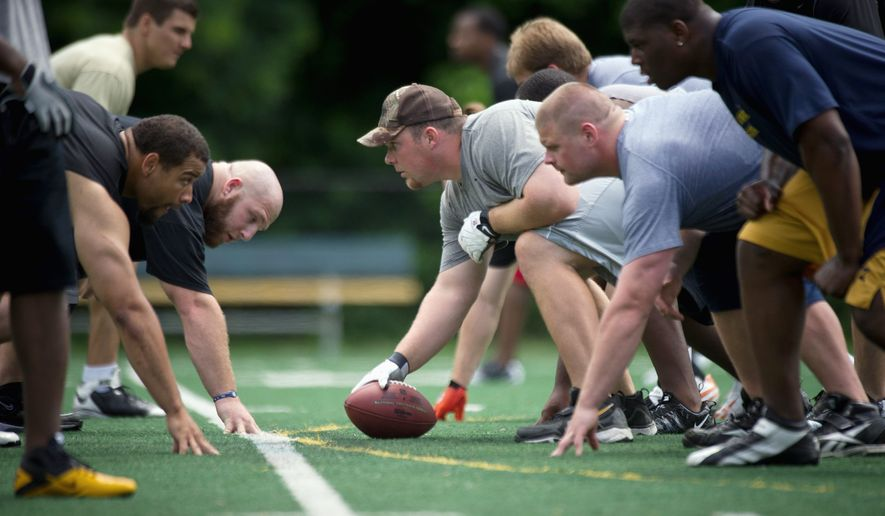 Will Montgomery (with ball) gets ready for a play on the line of scrimmage during an informal Redskins practice at a facility in Northern Virginia in June 2011. (Rod Lamkey Jr./The Washington Times)