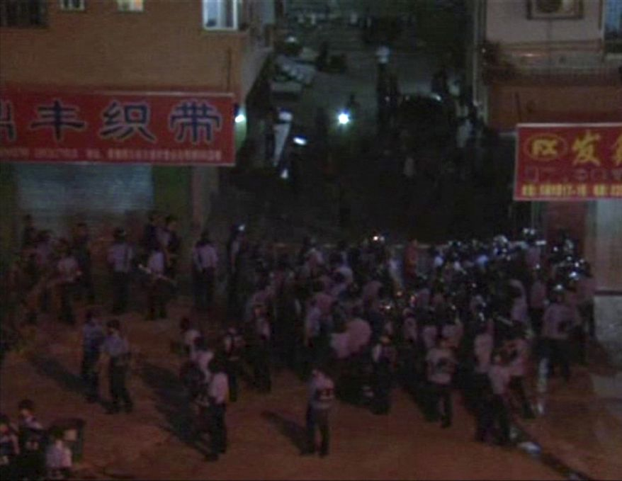 In an image made from video broadcast by Cable TV, helmeted anti-riot police try to arrest protesters in Xintang, in southern China's Guangdong Province, on Sunday, June 12, 2011. Demonstrators in the manufacturing hub torched emergency vehicles in an outburst of anger against police abuse of migrant workers, eyewitnesses said Monday. Sunday night's rioting followed three days of steadily growing unrest in the town. (AP Photo/Cable TV via Associated Press TV)