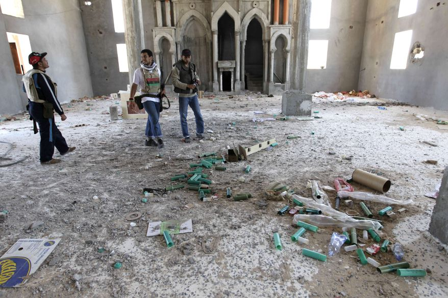 ** FILE ** Rebel fighters inspect the inside of a mosque thought to have been used by snipers loyal to Libyan leader Moammar Gadhafi, after heavy clashes with pro-Gadhafi forces on the front line at Dafniya, about 25 miles (40 kilometers) west of Misrata, Libya, Monday, June 13, 2011. (AP Photo/Hassan Ammar)
