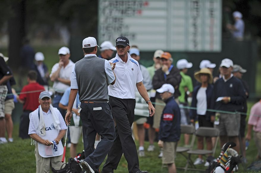 Michael Tobiason, Jr., of Wilmington, Del. fist bumps Jesse Hutchins after Hutchins birdied the first hole during the first round of the U.S. Open at Congressional Country Club in Bethesda, Md., Thursday, June 16, 2011. (Rod Lamkey, Jr./The Washington Times)