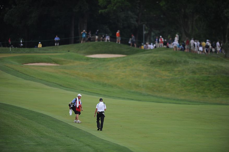 Caddie Gerry Thornton and Michael Tobiason, Jr., of Wilmington, Del. walk up the 4th fairway during the first round of the U.S. Open at Congressional Country Club in Bethesda, Md., Thursday, June 16, 2011. (Rod Lamkey, Jr./The Washington Times)
