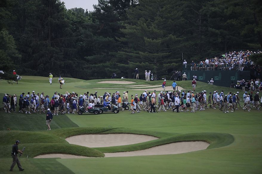Members of the gallery cross the fairway between groups during the first round of the U.S. Open at Congressional Country Club in Bethesda, Md., Thursday, June 16, 2011. (Drew Angerer/The Washington Times)