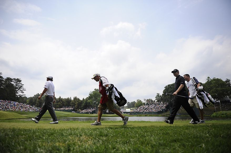 Stephen Gallacher of Scotland, left, and Jason Dufner, right in black, make their way to the 10th green around a water hazard during the first round of the U.S. Open at Congressional Country Club in Bethesda, Md., Thursday, June 16, 2011. (Drew Angerer/The Washington Times)