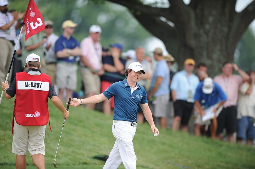 Tournament leader Rory McIlroy, of Northern Ireland, hands his putter to his caddie after sinking a birdie put during the first round of the U.S. Open at Congressional Country Club in Bethesda, Md., Thursday, June 16, 2011.  (Rod Lamkey, Jr./The Washington Times)