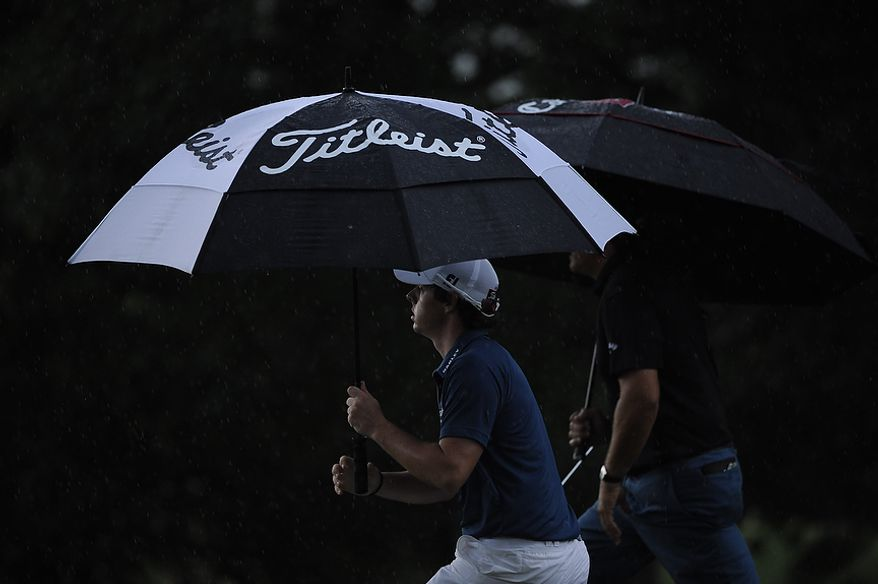 Tournament leader Rory McIlroy, of Northern Ireland, makes his way through the rain on the 9th hole during the first round of the U.S. Open at Congressional Country Club in Bethesda, Md., Thursday, June 16, 2011. He finished with a 6-under 65.  (Drew Angerer/The Washington Times)