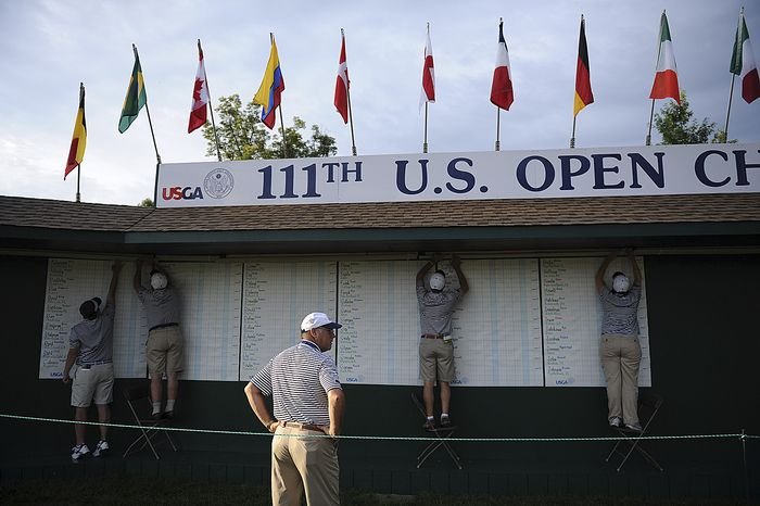 Course workers post the pairings and scoreboard before the first round of the U.S. Open at Congressional Country Club in Bethesda, Md., on Thursday, June 16, 2011. (Rod Lamkey Jr./The Washington Times)