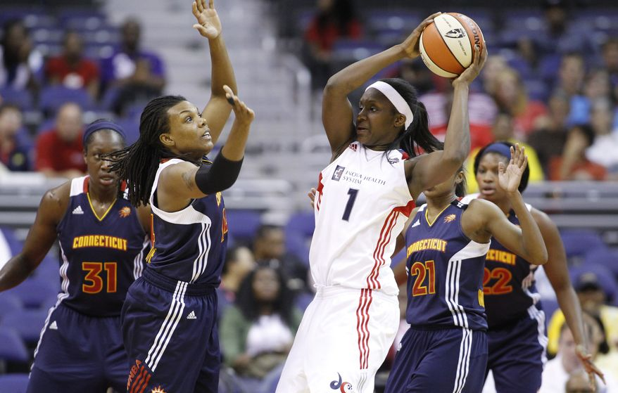 Washington Mystic's' Crystal Langhorne (1) looks to pass the ball as Connecticut Sun's Tina Charles (31), Tan White, second from left, and Renee Montgomery (21) defend during the first quarter of a WNBA basketball game on Thursday, June 16, 2011, in Washington. Mystics lost 89-81. (AP Photo/Luis M. Alvarez)