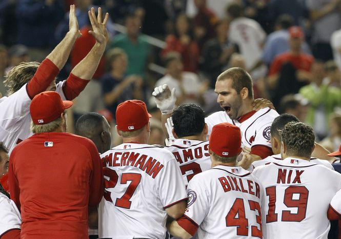 Washington Nationals' Danny Espinosa, top right, leaps into a pile of teammates after hitting a walk-off home run off St. Louis Cardinals reliever Fernando Salas during the 10th inning of a baseball game in Washington, Thursday, June 16, 2011. The Nationals beat the Cardinals 7-4. (AP Photo/Ann Heisenfelt)