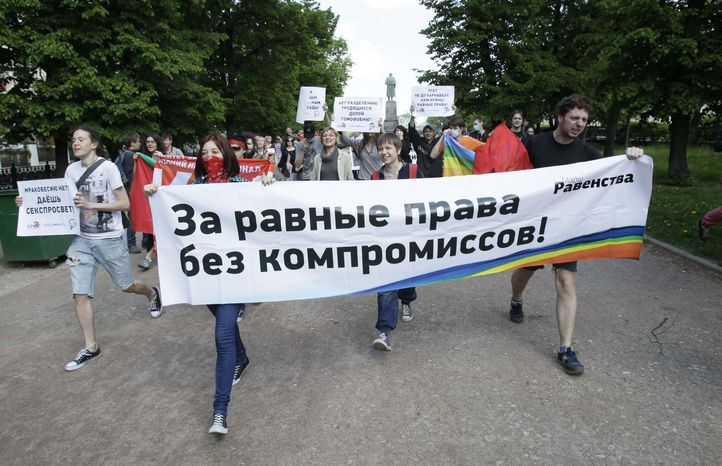 """** FILE ** Young people hold a banner that translates as """"For equal rights without compromise"""" during an equality march in downtown Moscow on Sunday, May 22, 2011. The demonstrators protested against discrimination based on sex or gender orientation and called for equal rights for women and members of the lesbian, gay, bisexual and transgender community. (AP Photo/Ivan Sekretarev)"""