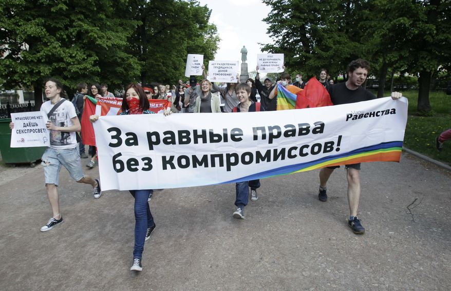 "** FILE ** Young people hold a banner that translates as ""For equal rights without compromise"" during an equality march in downtown Moscow on Sunday, May 22, 2011. The demonstrators protested against discrimination based on sex or gender orientation and called for equal rights for women and members of the lesbian, gay, bisexual and transgender community. (AP Photo/Ivan Sekretarev)"