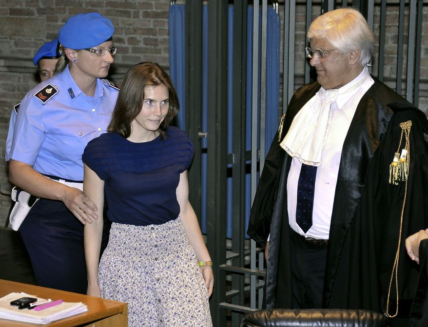 Amanda Knox, second from left, walks past her lawyer Luciano Ghirga, as she arrives in court for the appeal trial in Perugia, Italy, Saturday, June 18, 2011. Knox was convicted of murdering her British roommate in Perugia, Meredith Kercher, and sentenced to 26 years in prison. (AP Photo/Stefano Medici)