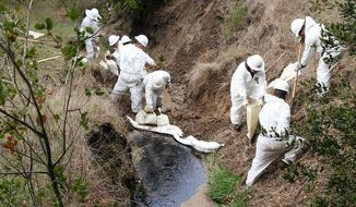 In this file photo, a Greka Oil & Gas cleanup crew works on an oil spill flowing down a creek behind Firestone Vineyard, north of Los Olivos, Calif. in January 2008. On April 11, 2018, California regulators hit the troubled company with a record $12.5 million fine following nearly 1,500 violations in the past year at an oil field in Orange County. (Santa Barbara County Fire Department via Associated Press) **FILE**