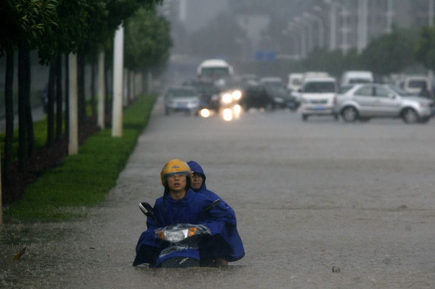 Two men on a motorcycle are stuck in floodwaters in Wuhan in central China's Hubei province on June 18, 2011. (Associated Press)