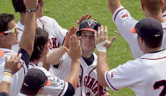 Virginia's Keith Werman, center, celebrates with teammates after he scored in the seventh inning of an NCAA College World Series baseball game against California on a single by John Hicks, in Omaha, Neb., Sunday, June 19, 2011. Virginia won 4-1. (AP Photo/Nati Harnik)