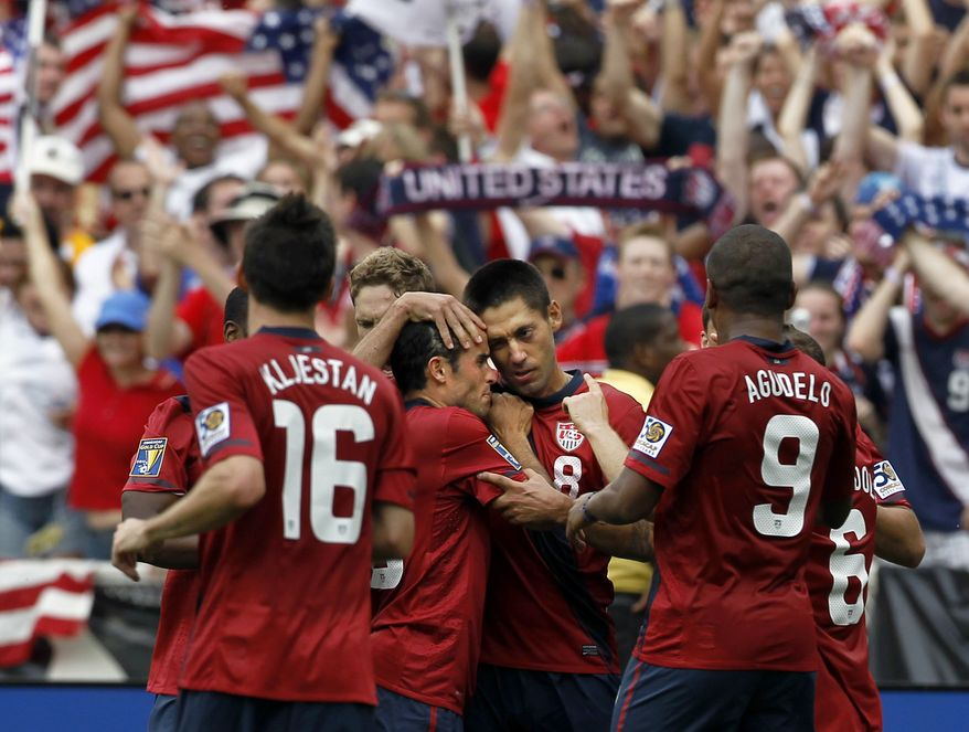 United States' Clint Dempsey (8) is surrounded by his teammates after his goal during the second half of a CONCACAF Gold Cup quarterfinal soccer match with Jamaica on Sunday, June 19, 2011 at RFK Stadium in Washington. The United States won 2-0. (AP Photo/Alex Brandon)