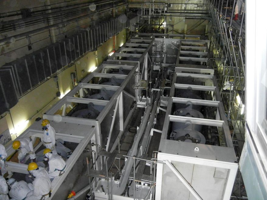 **FILE** In this photo from June 1, 2011, workers inspect equipments inside the cesium absorption tower, part of the radioactive water processing facilities at Fukushima Dai-ichi nuclear power plant in Okuma, Fukushima Prefecture, northeastern Japan. (Associated Press/Tokyo Electric Power Co.)