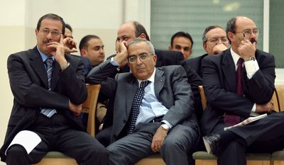 **FILE** In this photo taken on Nov. 12, 2003, then Palestinian Finance Minister Salam Fayad (center), former government General Secretary Hasan Abu-Lebdeh (right) and former Labor Minister Ghassan Khatib (left) sit in an unknown office in the West Bank city of Ramallah. (Associated Press)