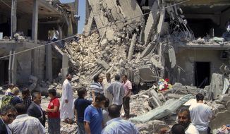 In this photo taken on a government-organized tour, members of the media and others examine the remains of a damaged residential building in Tripoli, Libya, on June 19, 2011. (Associated Press)