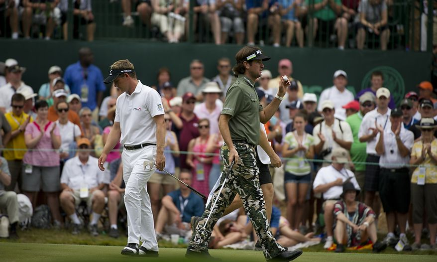 Luke Donald (left) prepares for his shot while Bubba Watson (right)acknowledges the crowd on the sixth green during the championship round of the 2011 U.S. Open Congressional, in Bethesda, Md., Sunday, June 19, 2011. (Rod Lamkey Jr./The Washington Times)
