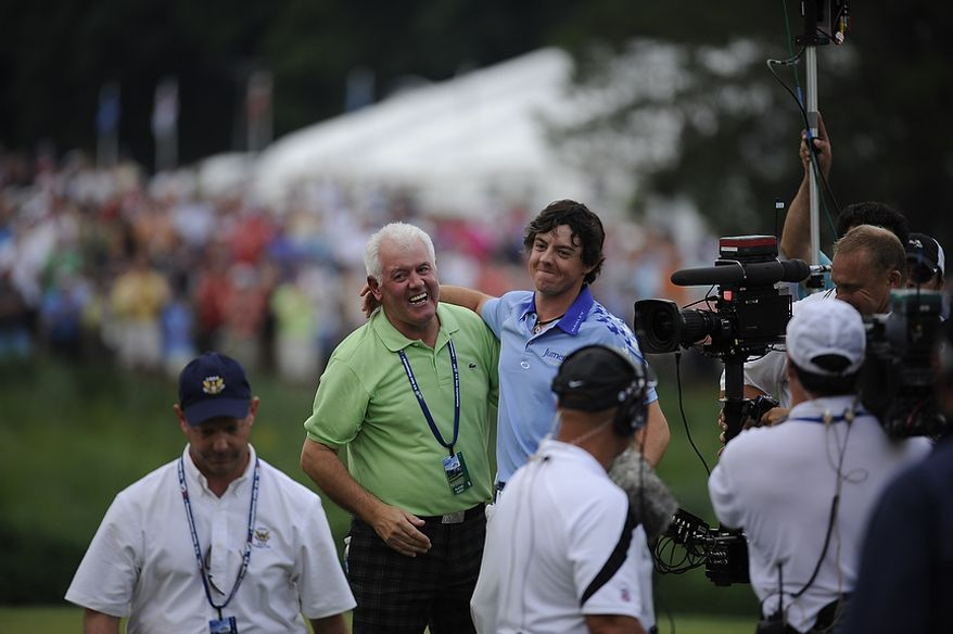 Rory McIlroy, of Northern Ireland, hugs his father Gerry McIlroy after winning the U.S. Open at Congressional Country Club in Bethesda, Md., Sunday, June 19, 2011. (Drew Angerer/The Washington Times)