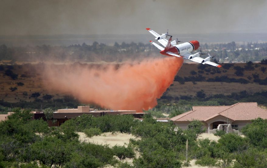 A plane drops slurry near houses after a fire sparked on Fort Huachuca in Sierra Vista, Ariz., on June 17, 2011. (Associated Press/Arizona Daily Star)