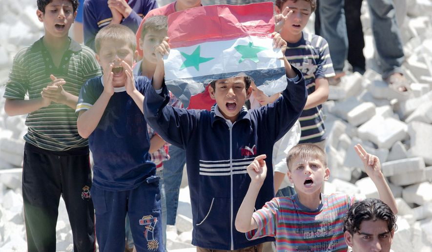 Children hold a handmade Syrian flag during a protest against President Bashar Assad's speech in a refugee camp across the border in Yayladagi, Turkey. Mr. Assad said Monday that his regime would consider political reforms, but opponents said his words lacked any clear sign of a transition to democracy. (Associated Press)